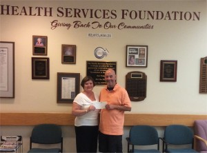 Don Collins, right, chairman of the County Open, presents a $20,000 check to Elizabeth Dulin, executive director of the Health Services Foundation.